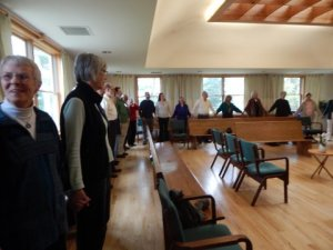 Linking hands to sing grace before potluck lunch.
